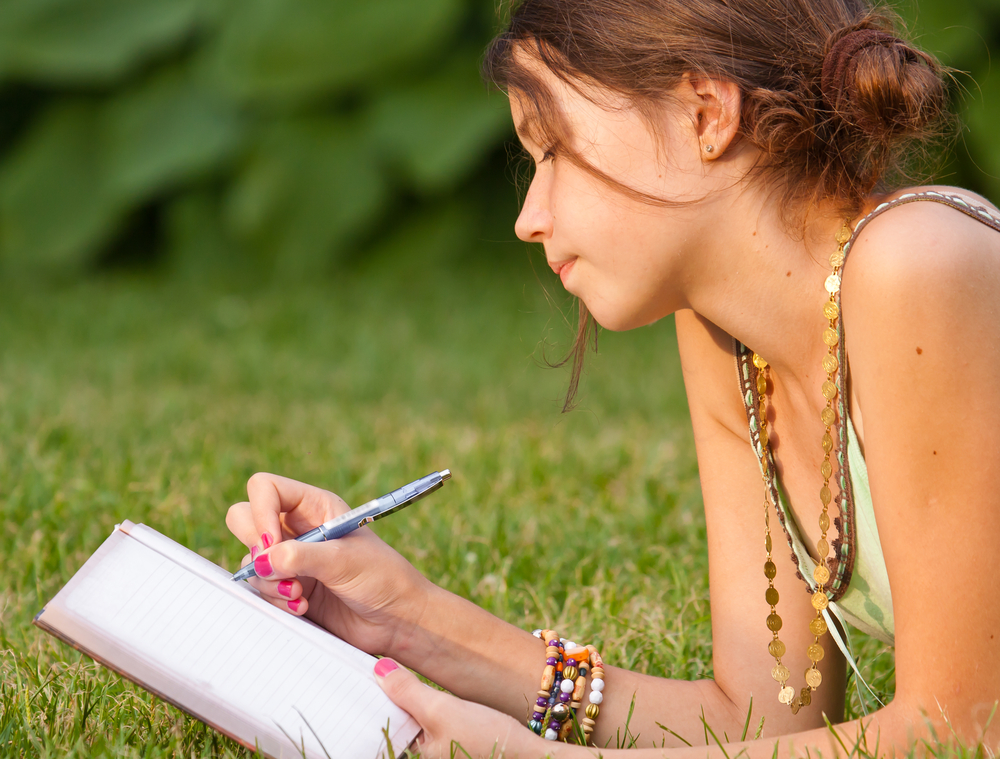 Sexy young woman writing diary while stock photo