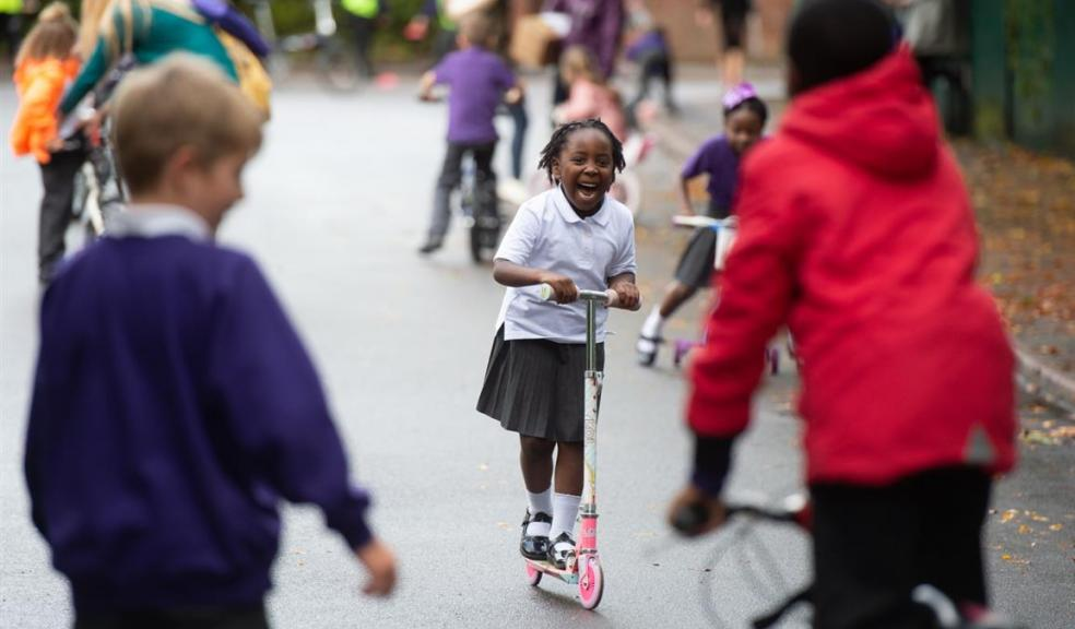 Photo of children playing on scooters and bikes