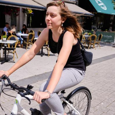 Woman cycling on high street that has been closed to motor traffic