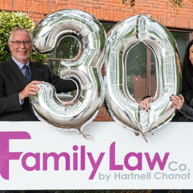 Two solicitors from The Family Law Company holding celebration balloons